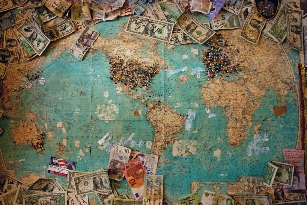 A Map surrounded by all the cash you could save with these travel tips to save money.